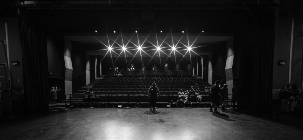 A black and white image of a person standing on a stage to an almost empty audience